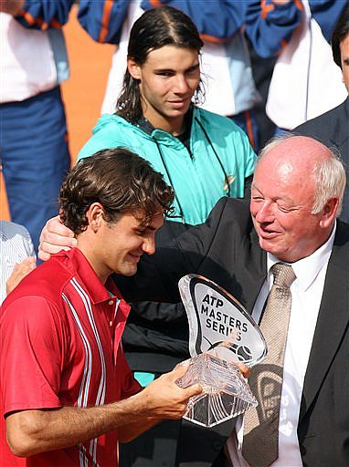 Federer feliz con su trofeo, es felicitado por el director del torneo; al fondo Nadal observa