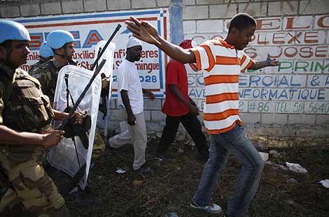 Los cascos azules dispersan a los haitianos que se acercan en busca de agua. | Reuters