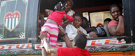 Una niña, aupada a un autobús para huir de la capital. | Reuters Más imágenes