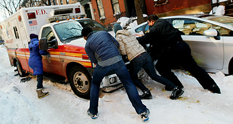 Peatones y trabajadores de emergencias intentan mover una ambulancia en Brooklyn. | AFP