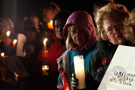 Manifestantes con velas y carteles en una vigilia por el 32 aniversario de Three Mile Island. | AFP