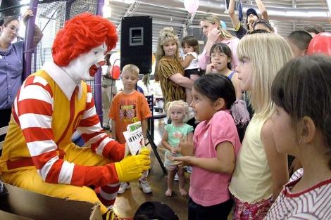 El payaso de McDonald's juega con unos niños en uno de sus restaurantes. | AP
