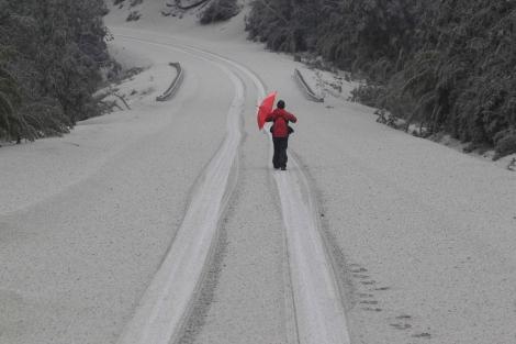 Un hombre camina por una carretera cubierta de cenizas. I Reuters