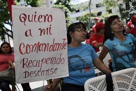 Dos mujeres muestran su apoyo al presidente Hugo Chávez.   AP