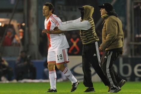 Adalberto Roman de River Plate es acosado por un hincha. | Ap
