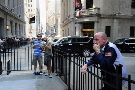 Un operador de bolsa toma su descanso mientras dos turistas posan para una foto. | AFP