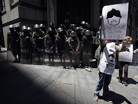 Una mujer sostiente un cartel contra Evo Morales en La Paz. | Reuters