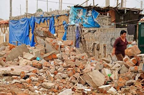 Una mujer mientras camina entre los escombros dos semanas después del sismo de 2007. | Efe
