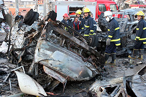 Bomberos junto al coche bomba a las puertas de la universidad. (Foto: AP)