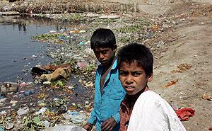 Dos niños buzos se ganan la vida sumergiéndose para recolectar las monedas que arrojan la gente al Río Yamuna en Nueva Delhi. (EFE)