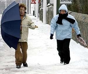 Dos mujeres pasean con un fuerte viento y el piso nevado en Salces, en Cantabria. (Foto: EFE)