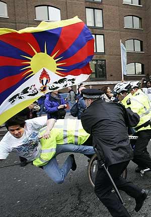 La policía londinense neutraliza a un activista al paso de la antorcha. (Foto: AP)