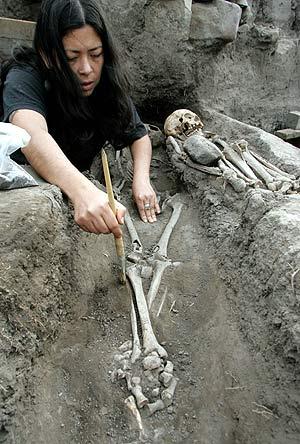Una arqueóloga trabaja en uno de los esqueletos. (Foto: AFP)