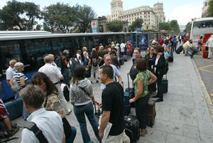 Decenas de personas hacen cola en plaza Catalunya para coger el bus al aeropuerto. (Foto: Antonio Moreno)