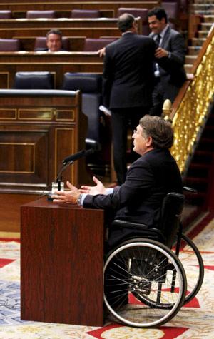 En la imagen el diputado Francisco Vañó junto a la inaccesible tribuna de oradores del parlamento, con una mesa y unos micrófonos preparados para la ocasión