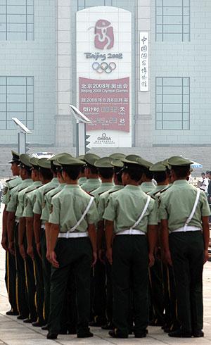Un cuerpo de policía forma frente a un cartel de los JJOO. (Foto: REUTERS)