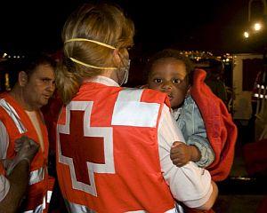 Un miembro de la Cruz Roja sostiene al único bebé superviviente de los que viajaban en la patera rescatada. (Foto: EFE)