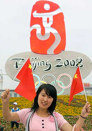 Una mujer china posa para una foto delante del logotipo 'Baila Pekín' de los JJOO'08 en la plaza de Tiananmen, en Pekín. (Foto: EFE)