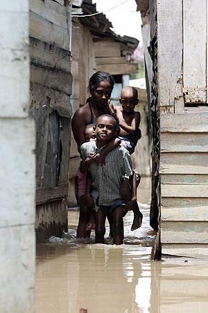 iembros de una familia transitan entre las casas inundadas, en el barrio La Lata, en República Domincana. (Foto: EFE)