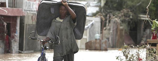 Un hombre de la ciudad haitiana de Gonaives huye del agua con una bici y una maleta. (Foto: AP)