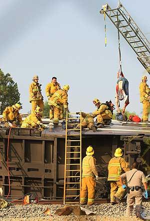 El cuerpo de uno de los pasajeros es sacado del tren por los bomberos. (Foto: AP)