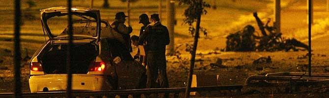 Un agente de la Ertzaintza y personal de Emergencias, en las inmediaciones del lugar del atentado. (Foto: EFE)