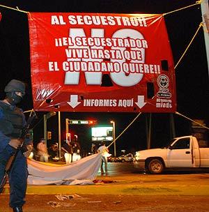 Hace días, un periodista moría a tiros mientras colocaba esta pancarta contra los secuestros. (Foto: EFE)