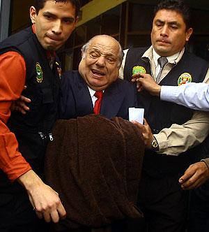 Alberto Quimper (c), ex miembro del directorio de Perúpetro, encargada de las licitaciones petroleras, es trasladado por las fuerzas del orden. (Foto: EFE)
