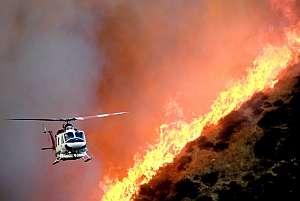 Un helicóptero del Departamento de Bomberos de Los Angeles sobrevuela una zona incendiada. (Foto: EFE)