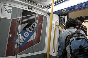 Dos viajeros de la línea 3 se bajan en una de las estaciones. (Foto: Jaime Villanueva)