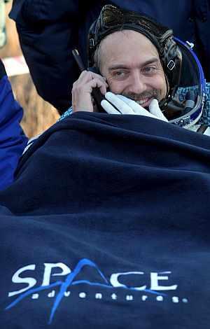 Richard Garriott habla por teléfono después de aterrizar en Kazajistán. (Foto: EFE)