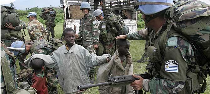 Soldados uruguayos de la ONU, con unos niños en Kibati, a 12 km de Goma. (Foto: AP). Más imágenes