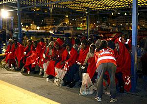 Varios de los 68 inmigrantes son atendidos por miembros de la Cruz Roja. (Foto: EFE)