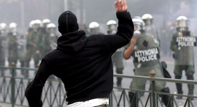 Un joven lanza un objeto a la policía en uno de los enfrentamientos. (Foto: EFE).