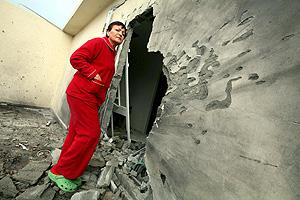 Una mujer israelí observa los desperfectos causados en su casa de Sderot por un proyectil palestino. (Foto: EFE)