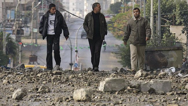 Tres palestinos caminan por una destrozada calle de Gaza. (AP)