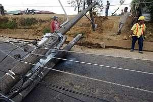 Miembros del cuerpo de socorro tratan de abrir paso entre los daños y derrubes en San Isidro de Alajuela. (Foto: EFE)
