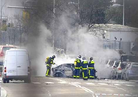 Varios bomberos extinguen las llamas en un coche afectado por la explosión. | Foto: AFP