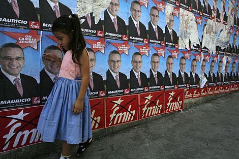 Una niña salvadoreña, ante carteles electorales de Funes. | AP