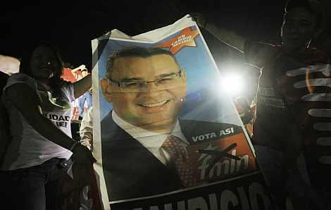 Partidarios de Funes portan una pancarta con su foto. | Efe