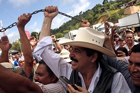 Zelaya (con sombrero) levanta la cadena que separa la frontera. | AFP