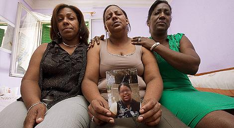 Amarilis, la madre de la niña asesinada el sábado en Madrid, sostiene una foto de su pequeña, acompañada de sus hermanas Luisa y Lucía. | Gonzalo Arroyo
