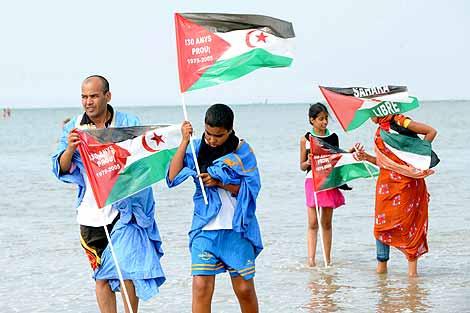 Varios saharauis con banderas del Polisario en una playa francesa. | AFP