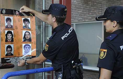 Dos miembros de la Policía Nacional retiran un cartel con los rostros de seis etarras ya detenidos. | Efe