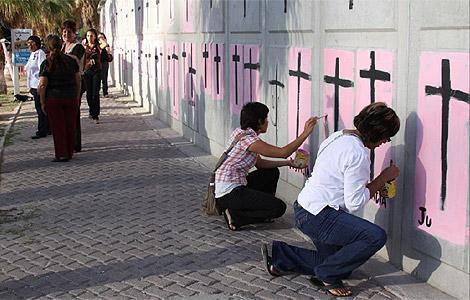 Varias mujeres pintan cruces de protesta en Juárez. | Efe