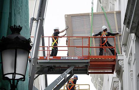 Dos operarios introducen uno de los paneles de Sorolla. | Efe