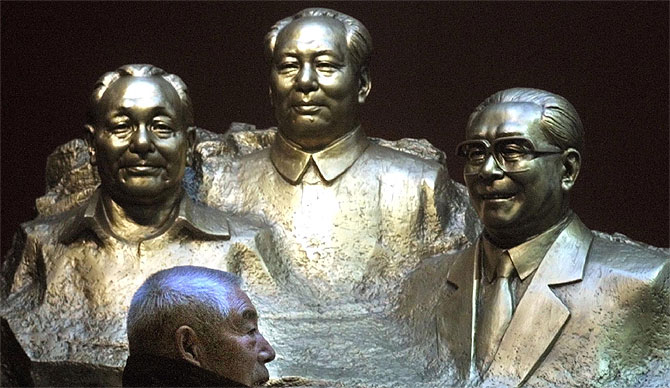 Un hombre pasa junto a un grupo escultorico que representa a Deng Xiao Ping. Mao Zedong y Jian Zeming en Beijing. (Foto: AP)