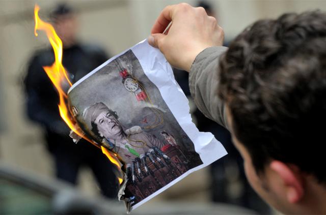Un hombre quema una imagen de Gadafi en el Consulado de Libia en París. | Reuters