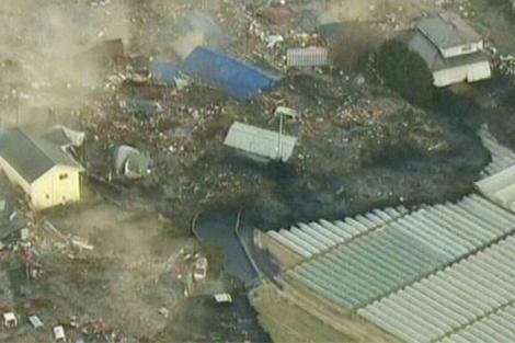 Momento en el que una gran ola arrasa la localidad de Sendai.   AP