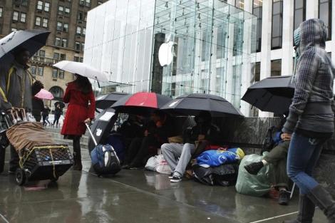 Varias personas hacen cola frente a una tienda de Apple en Nueva York. | Reuters.
